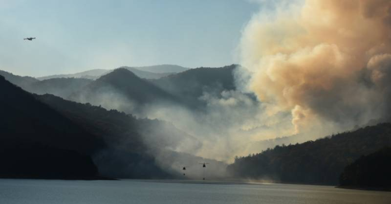 Helicopters scooping water from reservoir with fire in the background.